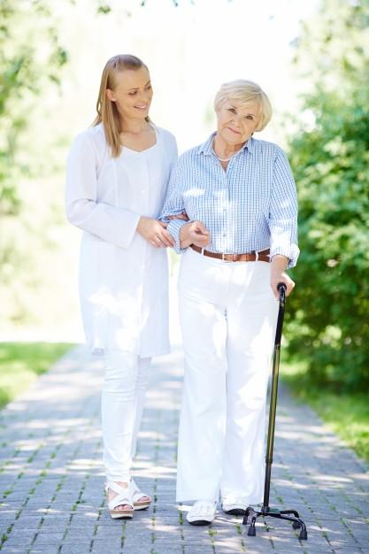 Nurse helping senior woman with walking stick Free Photo